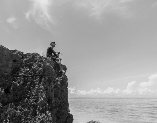 A man on a cliff talking to himself and looking ahead